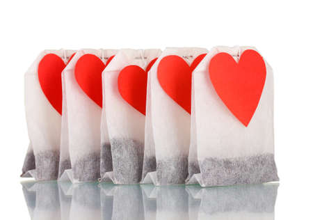 Tea bags with blank heart-shaped labels isolated on white photo