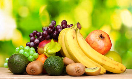 Assortment of exotic fruits on wooden table on green background photo