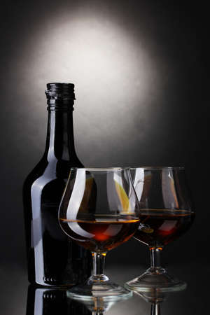 Glasses of brandy and bottle on gray background photo