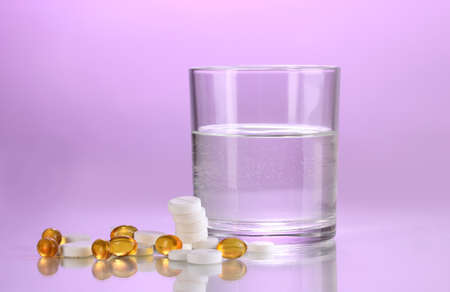 Glass of water and pills on purple background Stock Photo - 12330066