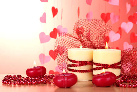 Beautiful candles with romantic decor on a wooden table on a red background photo