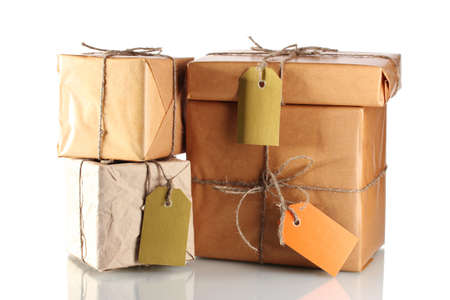 Many parcels wrapped in brown paper tied with twine and with blank labels isolated on white photo