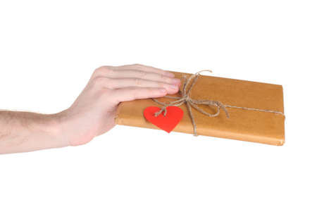 Parcel with blank heart-shaped label in mans hand isolated on white photo