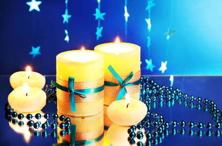 Beautiful candles, gifts and decor on blue background photo