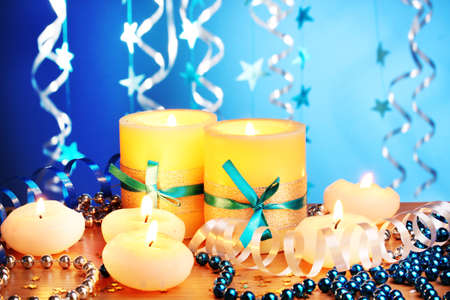 Beautiful candles, gifts and decor on wooden table on blue background Stock Photo - 12430523