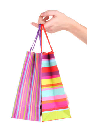 bright gift bags in hand isolated on white photo