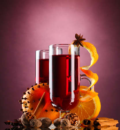 mulled wine in the glasses, spice and orange on purple background photo