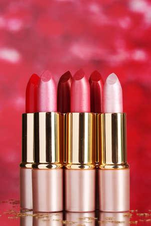 beautiful lipsticks on red background photo