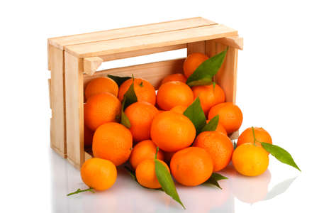 wooden box: Ripe tasty tangerines with leaves in wooden box dropped isolated on white Stock Photo