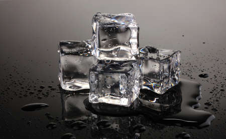 cubetti di ghiaccio: Cubetti di ghiaccio di fusione su sfondo grigio Archivio Fotografico