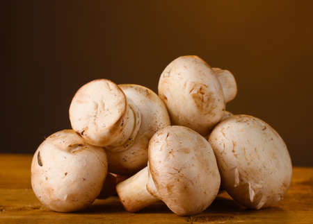 champignons mushrooms in basket on wooden table on brown background Stock Photo - 12431777
