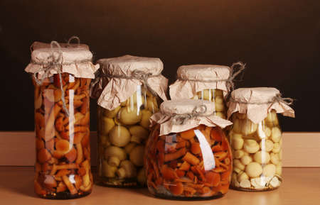 delicious marinated mushrooms in the glass jars on wooden shelf photo