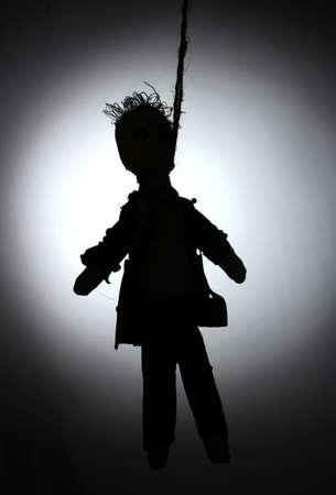 Hanged doll voodoo boy-groom on grey background photo