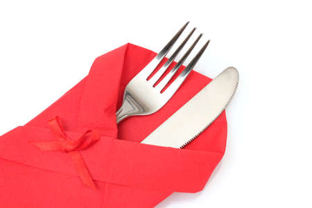 servilleta de papel: Tenedor y cuchillo en una tela roja con un arco aislado en blanco