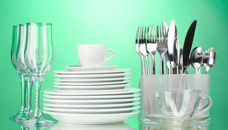 Clean plates, glasses, cup and cutlery on green background Stock Photo - 12436340