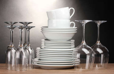 Clean plates, glasses and cups on wooden table on grey background photo
