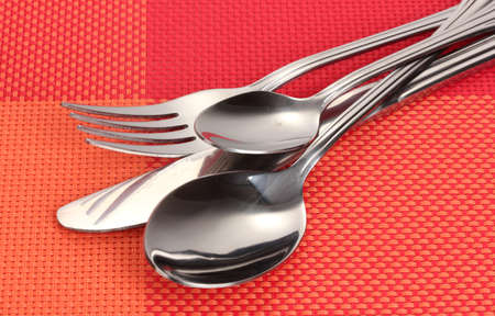 Fork, spoon and knife on a red tablecloth photo