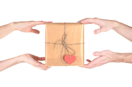 Woman's hand giving parcel with blank heart-shaped label to man isolated on white photo