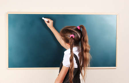 kids writing: beautiful little girl writing on classroom board