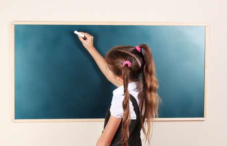 chalk writing: beautiful little girl writing on classroom board