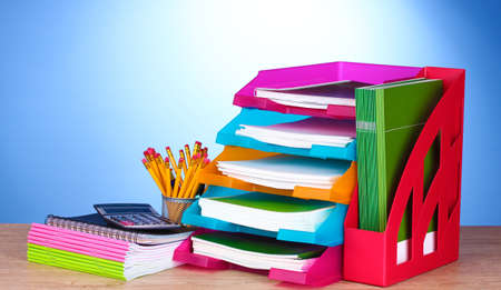 secretary tray: bright paper trays and stationery on wooden table on blue background