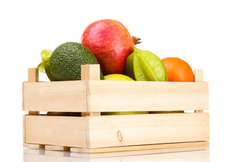 Assortment of exotic fruits in wooden box isolated on white photo