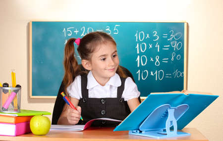 little schoolchild in classroom near blackboard photo