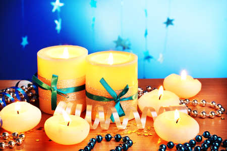 Beautiful candles, gifts and decor on wooden table on blue background photo