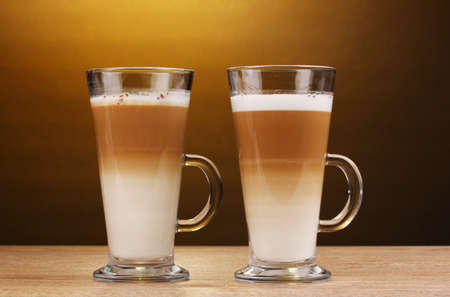 Fragrant сoffee latte in glass cups on wooden table on brown background photo