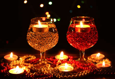 Amazing composition of candles and glasses on wooden table on bright background Stock Photo - 12436208