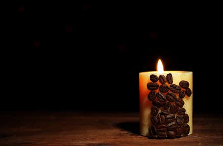 Beautiful candle with coffee beans on wooden table on black background photo