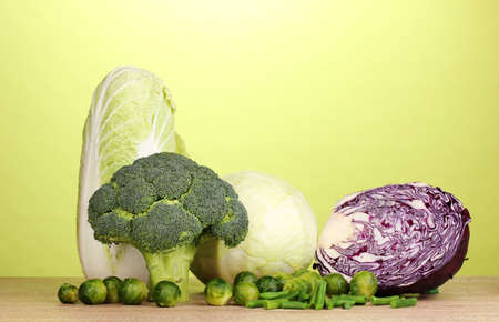 Fresh broccoli and cabbages on wooden table on green background photo