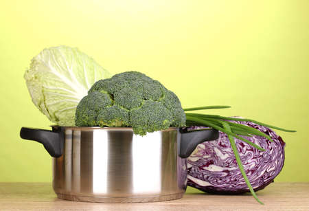 Saucepan with broccoli and cabbages on wooden table on green background Stock Photo - 12431703