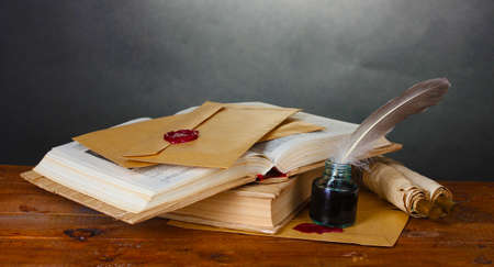 libri antichi, pergamene, penna d'oca e calamaio su tavola di legno su sfondo grigio
