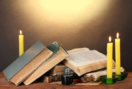 old desk: old books, scrolls, ink pen inkwell and candles on wooden table on brown background