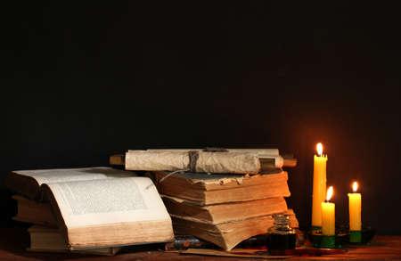 libros viejos: libros antiguos, pergaminos y tinta de la pluma tintero y velas en la mesa de madera sobre fondo marrón