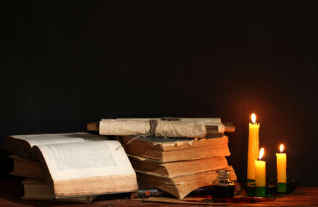wood pile: old books, scrolls, ink pen inkwell and candles on wooden table on brown background