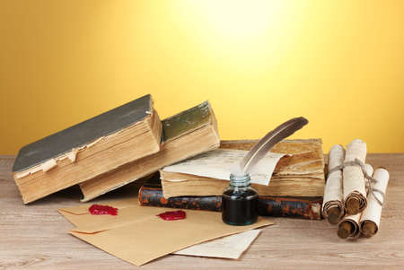 old books, scrolls, feather pen and inkwell on wooden table on yellow background Stock Photo - 12436168