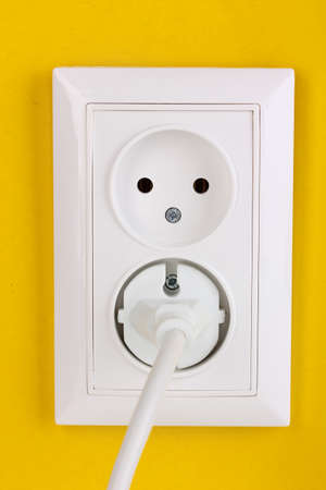 grounded plug: White electric socket with plug on the wall