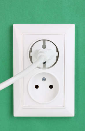 White electric socket with plug on the wall Stock Photo - 12436811