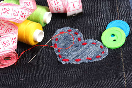 Heart-shaped patch on jeans with threads and buttons closeup Stock Photo - 12430893