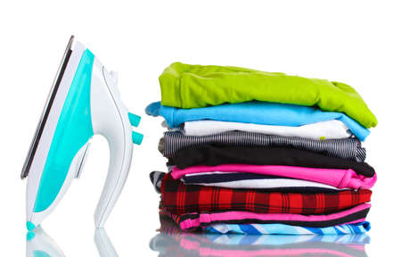 Pile of colorful clothes and electric iron isolated on white photo