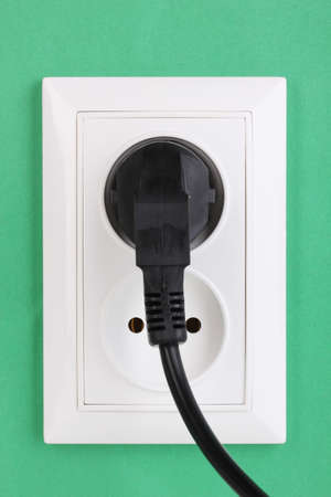 White electric socket with plug on the wall photo