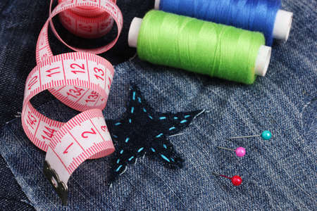 Star-shaped patch on jeans with threads and buttons closeup photo