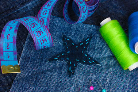 Star-shaped patch on jeans with threads and buttons closeup Stock Photo - 12553137