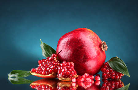 ripe pomegranate fruit with leaves on blue background