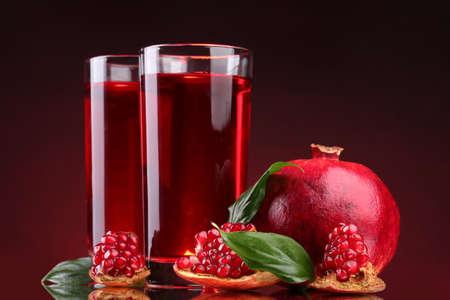 pomergranate: ripe pomergranate and glasses of juice on red background Stock Photo