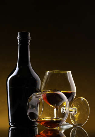 scotch: Glasses of brandy and bottle on yellow background