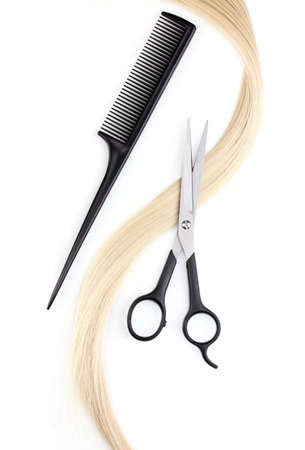 Shiny blond hair with hair cutting shears and comb isolated on white photo