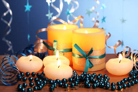 Beautiful candles, gifts and decor on wooden table on blue background Stock Photo - 12546203